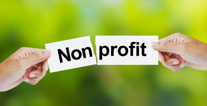 Businessman tearing the word Nonprofit for Profit
