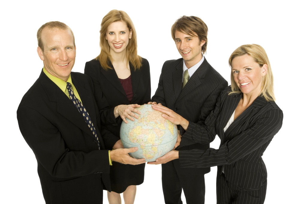 Business people hold a globe
